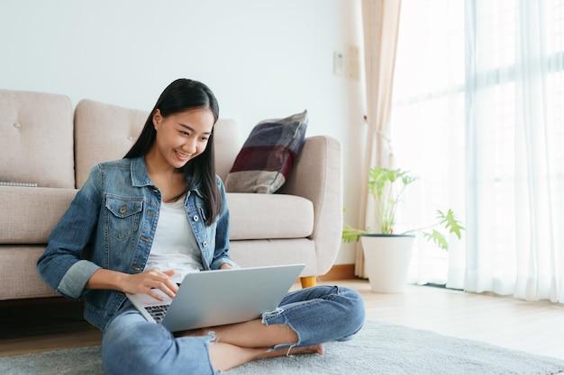 自宅の床に座ってラップトップを使用してジーンズを着ているアジアの女の子。