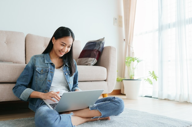 Asian girl wearing jeans using a laptop while sitting on the floor at home.