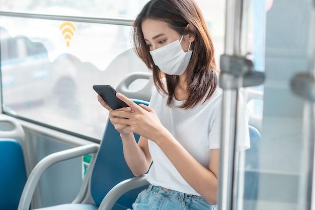 버스에서 스마트폰을 사용하는 동안 마스크를 쓴 아시아 소녀