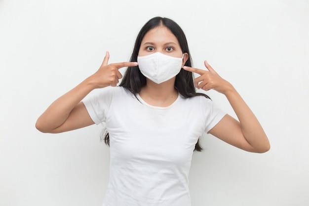 Азиатская девушка в медицинской маске для защиты от коронавируса covid19 позирует