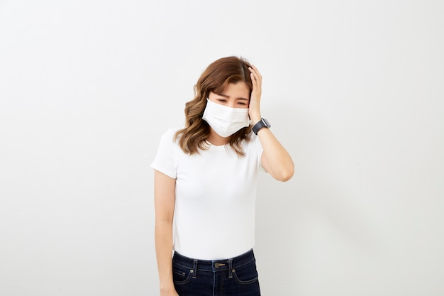 Asian girl wearing protective mask with headache