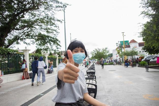 保護医療マスクを身に着けているアジアの女の子は、公共の場で親指を立てるジェスチャーをしますニューノーマル