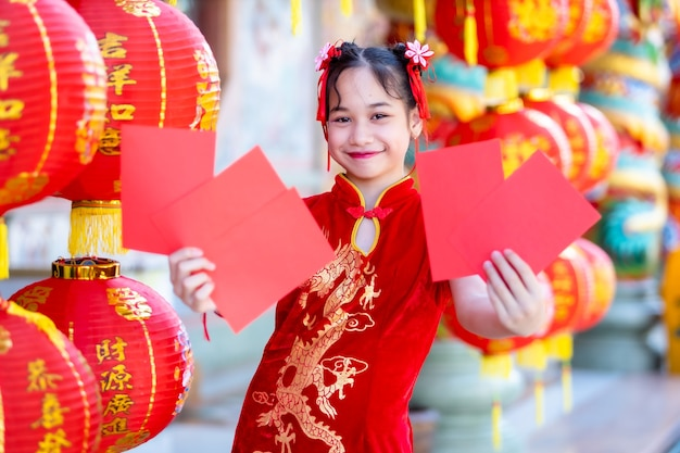 Asian girl wearing red traditional chinese cheongsam, holding red envelopes in hand and lanterns with the chinese text blessings written on it is a fortune blessing for chinese new year