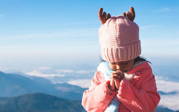 기도에 접힌 손을 만드는 스웨터와 따뜻한 모자를 쓰고 아시아 소녀