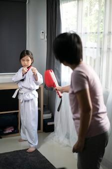 태권도 유니폼 연습을 입고 아시아 소녀는 집에서 한국 무술을 차기
