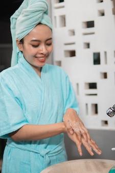 싱크대에 거품을 내기 위해 비누로 손을 씻는 동안 아시아 소녀는 목욕 타월을 착용합니다.