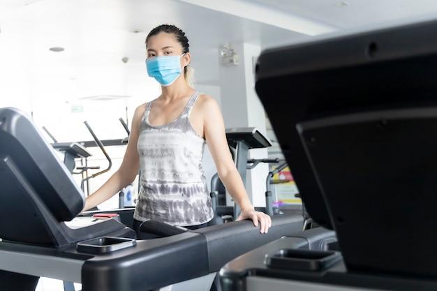 아시아 소녀는 신념 바이러스를 방지하기 위해 체육관에서 운동하기 위해 해부학 마스크를 착용