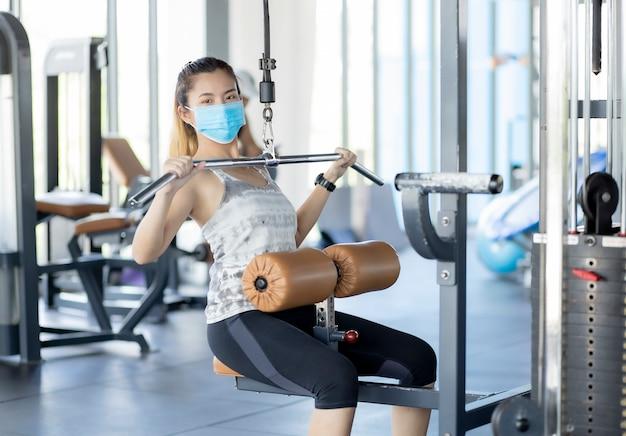 Азиатская девушка носит анатомическую маску, чтобы тренироваться в тренажерном зале, чтобы не поверить в вирусы