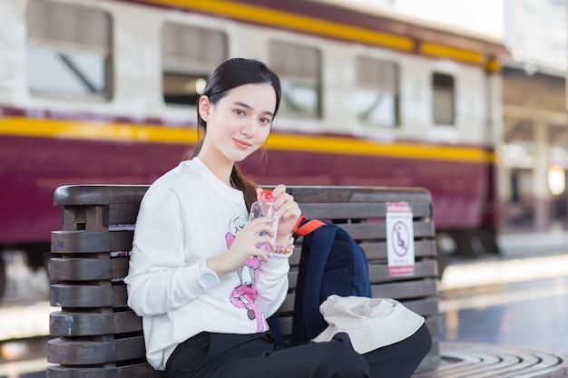 白い長袖を身に着けているアジアの女の子は椅子に座って、旅行から試してみたと感じます