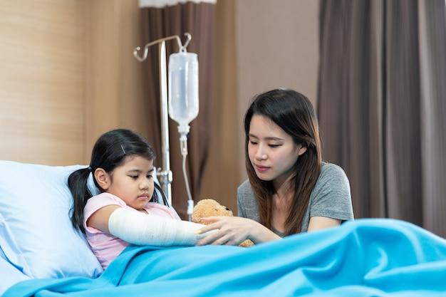 彼女の母親と一緒に病院のベッドでギプスを身に着けている腕を骨折したアジアの女の子