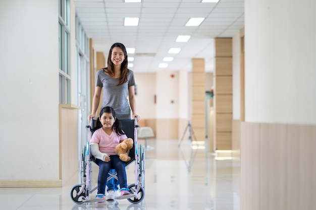 病院で彼女の母親と車椅子のキャスト設定を身に着けている腕を骨折したアジアの女の子