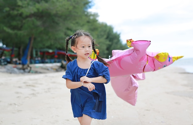 Asian girl with balloons on the beach