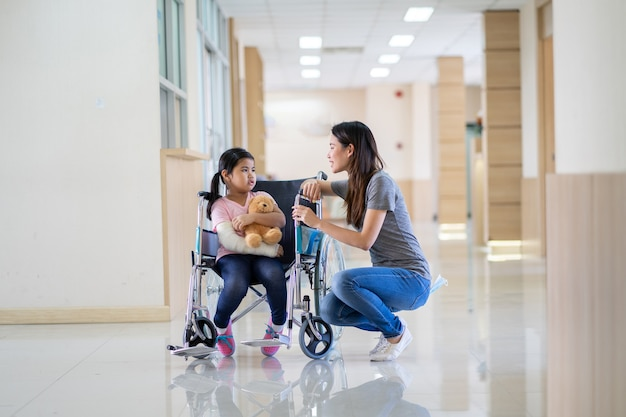 Asian girl with a broken arm wearing a cast setting on wheelchair with her mother at hospital
