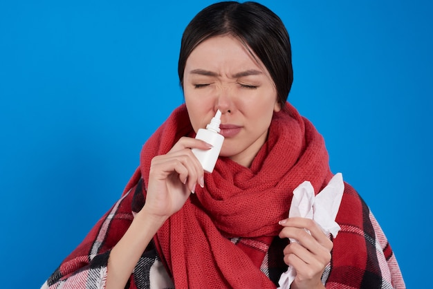 Asian girl with cold using nasal spray isolated