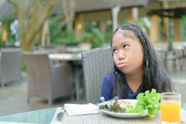 Asian girl with expression of disgust against vegetables