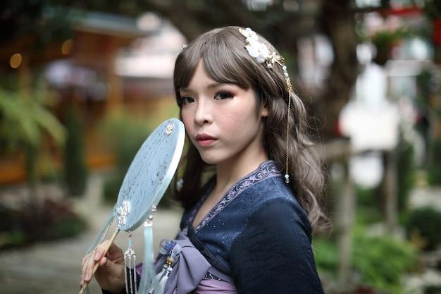 庭の背景にロリータファッションドレスとアジアの女の子