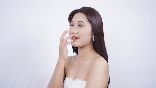 Азиатская девушка с макияжем, посмеиваясь, закрывает рот рукой, изолированной на белом фоне
