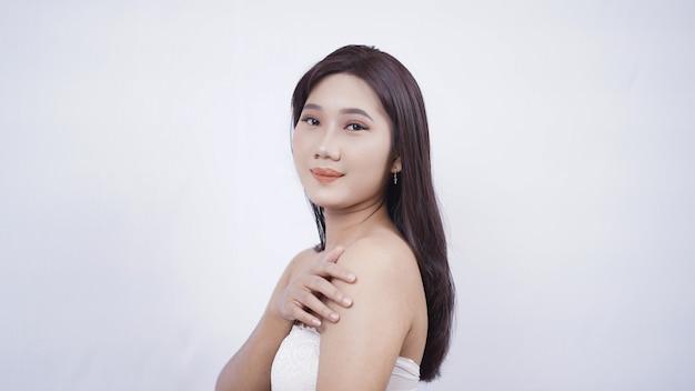 Азиатская девушка с макияжем, сладко улыбаясь рука боком плечо, изолированные на белом фоне
