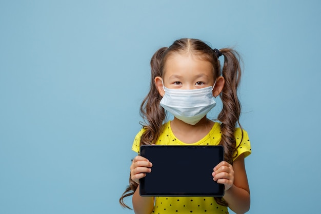An asian girl with a mask on her face holds a tablet in her hands in the studio on a blue