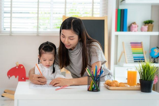 Asian girl with mother painting picture in book