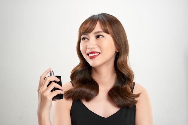 香水を持つアジアの女の子、彼女の手首に香水を適用し、においがする若い女性