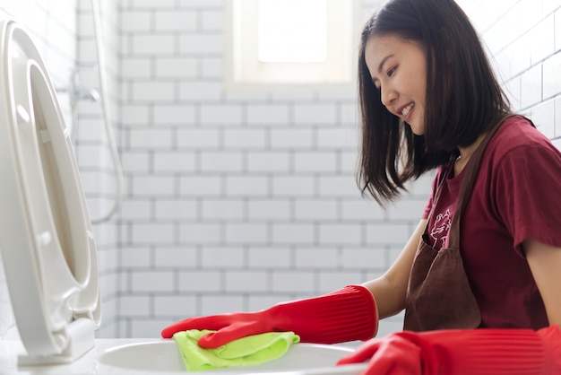 Asian girl with red rubber gloves is cleaning toilet bowl.