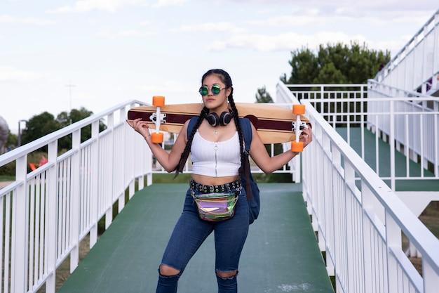 Азиатская девушка со скейтбордом и солнцезащитными очками