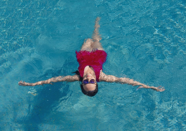 Asian girl with swimming suite and sun glasses on pool