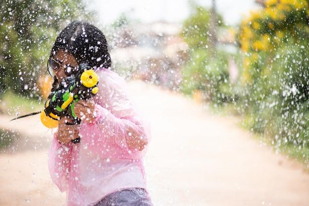 ソンクラーン祭り - タイの水祭りで水の銃を持つアジアの女の子。