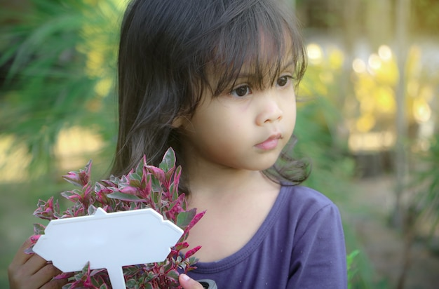 Asian girl with white label in the garden
