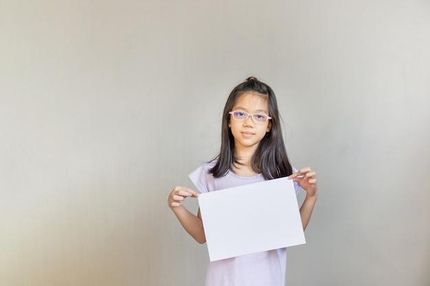 白い紙のアジアの女の子、空の白紙を保持している女の子、メッセージクリエイティブデザインコンセプトの空白のサインをモックアップします。