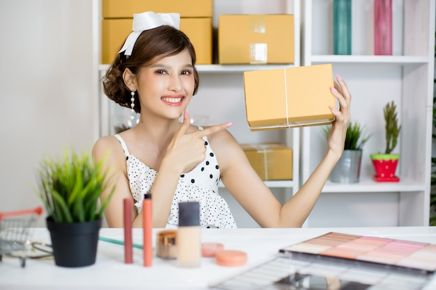 Asian girl  working at home office and sorting parcel post box to delivery service to customer