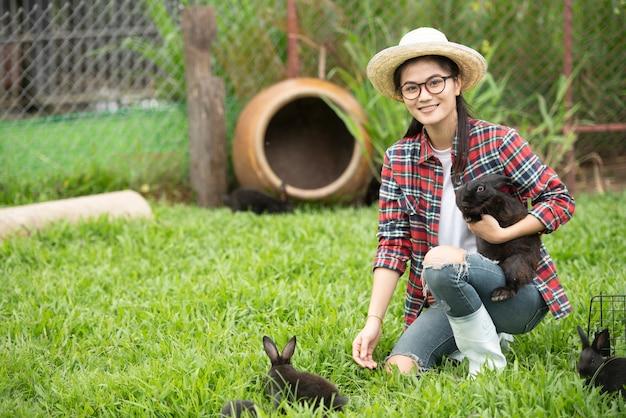 Asian girl working at rabbit  farm