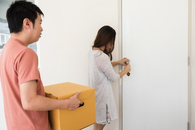 Asian girlfriend open front door by key while bofriend carry moving cardboard box