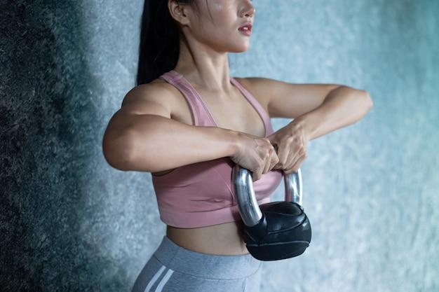 아시아 소녀들은 체육관에서 kettlebell과 함께 운동하고 있습니다.