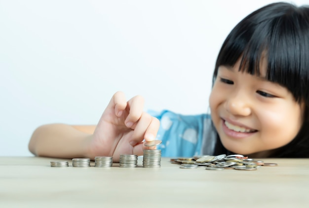 Asian girls are happy to arrange coins and count coins to save money with the white wall.