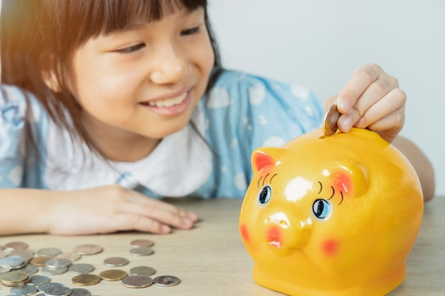 The asian girls are happy to drop the piggy bank to save money with the white wall. save money concept.