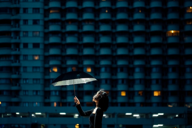 Asian girls in black are holding a glowing umbrella looking up at the sky at night in a city with lights.