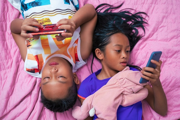 Asian girls and boys using smart phones on their bed at home during the day.