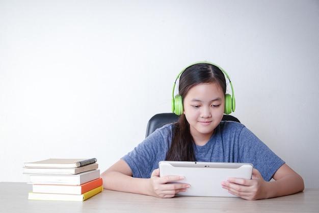 아시아 소녀들은 태블릿의 화상 통화 애플리케이션을 통해 집에서 온라인으로 배웁니다. 사회적 거리의 개념, 교육을 위한 기술 사용. 복사 공간