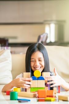 彼女は彼女の家、アジアの家族の概念で木製のブロックを再生しながら笑顔のアジアの女の子