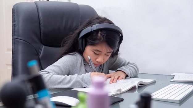 아시아 소녀들은 노트북으로 온라인으로 공부합니다. 아이는 격리에 대한 인터넷 수업을 사용하여 키보드 노트북을 입력하는 헤드셋을 착용합니다. 학생들은 학교 covid-19에서 인터넷 온라인 수업으로 배웁니다.