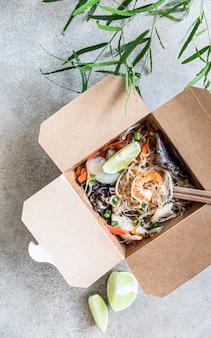 Азиатская стеклянная лапша с разными видами морепродуктов, овощами и грибами в одноразовой коробке