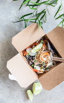 Asian glass noodles with different types of seafood vegetables and mushroom in disposable box