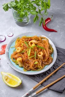 Азиатская стеклянная лапша с кальмарами и овощами на тарелке на столе.