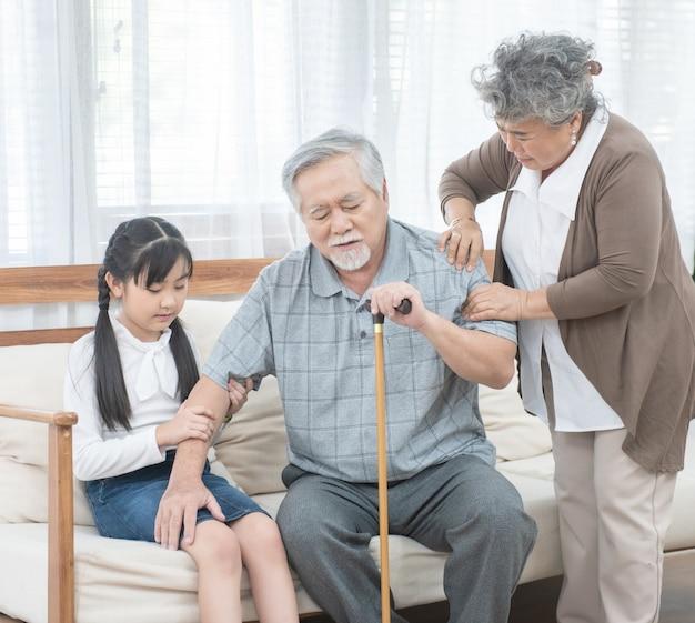 Азиатский дедушка падает вниз помощь и поддержка бабушки и внучки носят его сидеть на софе, концепция жизни выхода на пенсию