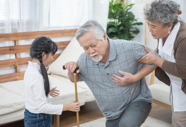 Азиатский дедушка падает бабушка и внучка помогают и поддерживают нести его, чтобы сидеть на диване