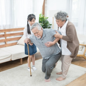 Asian grandfather fall down grandmother and granddaughter help and support carry him to sit on sofa