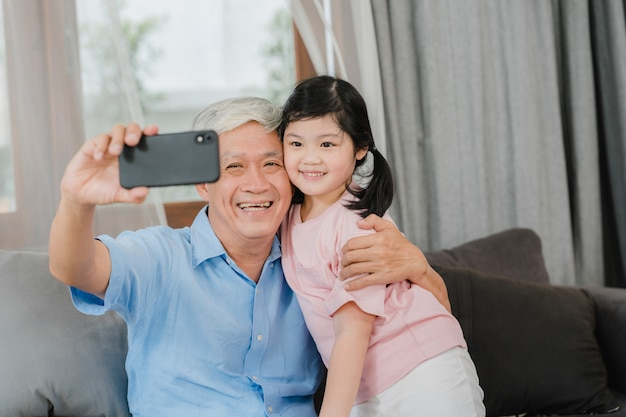 Asian grandfather and granddaughter video call at home. senior chinese grandpa happy with young girl using mobile phone video call talking with her dad and mom lying in living room at home.