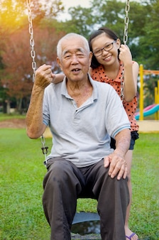 Asian grandfather posing with grandchildren
